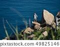 Traveler posing on stone on rocky seashore outdoors 49825146