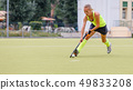 Young female field hockey player leading ball in attack. 49833208