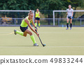 Young female field hockey player leading ball in attack. 49833244