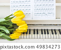 yellow tulips on a white piano with notes 49834273