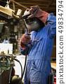Welder is welding in the garage,industrial Worker labourer at the factory welding steel structure 49834794