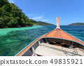 Wooden long-tail boat sailing on tropical sea 49835921