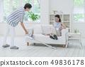 진공 청소기로 청소 남자와 소파에 앉아 다리를 올리는 여성 49836178