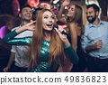 woman in a green dress is singing with her friends 49836823