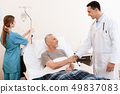 . The doctor shakes the old man's hand. 49837083