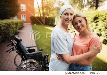 They embrace. Nearby is a wheelchair woman. 49837292