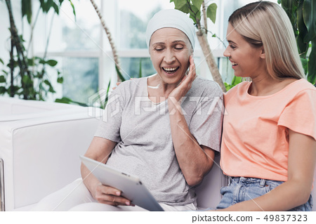 They are looking at something on a gray tablet. 49837323