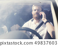 A young man with a beard sits at the wheel. 49837603