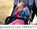 Little girl drinks juice from a bottle while 49840277