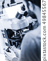 Scientist microscoping on fluorescent microscope. 49845567