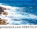 Waves hitting the sea shore rocks 49847019