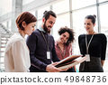 Group of young businesspeople standing near a staircase, talking. 49848736
