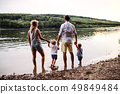 A rear view of family with two toddler children outdoors by the river in summer. 49849484