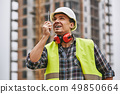 Turn left! Cheerful young builder in working uniform, yellow protective helmet talking to crane 49850664