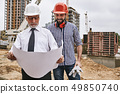 Perfect work. Main senior architect in formal wear and white helmet holding construction drawing and 49850740