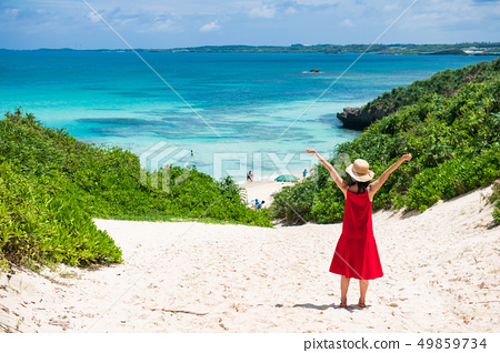 A woman walking along the road leading to the sea 49859734