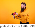 Bearded handyman in yellow hoodie holding power drill over yellow background. 49866999