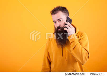 Bearded guy looking worried at the camera while talking on the phone over yellow background 49867138