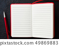 Empty open red notebook with red pen on dark 49869883