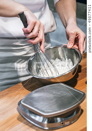 the Baker kneads the dough and mixes it with a whisk  49877411