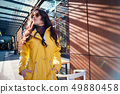 young woman in yellow raincoat at city street 49880458