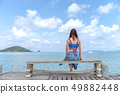 Woman sitting on a chair on the bridge in the sea 49882448