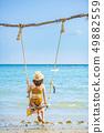 Women sitting on the beach swing, Koh Mak 49882559