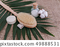 Soap, sea salt in glass bottle, natural brush and cotton flower on palm leaf background. 49888531