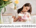 Young woman kiss baby during drinking milk 49888849