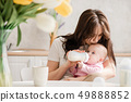 Young mother kiss his baby during drinking milk 49888852
