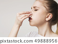 Young woman suffering from nose bleeding, panorama 49888956