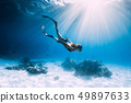 Woman freediver glides with fins. over sandy sea. 49897633