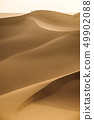 Vast expanses of desert and a small figure of a 49902088