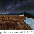 Night spring mountains and starry Milky Way 49910023