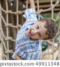 little boy climbing a rock wall outdoor. 49911348