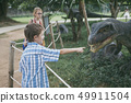 little boy playing in the adventure dino park. 49911504