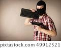 Man in balaclava holding keyboard and gun 49912521
