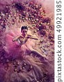 Young woman in pink ballet tutu surrounded by flowers 49921985