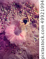 Young woman in pink ballet tutu surrounded by flowers 49921994