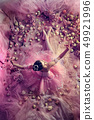 Young woman in pink ballet tutu surrounded by flowers 49921996