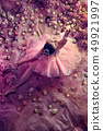 Young woman in pink ballet tutu surrounded by flowers 49921997