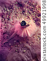 Young woman in pink ballet tutu surrounded by flowers 49921998