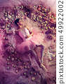 Young woman in pink ballet tutu surrounded by flowers 49922002