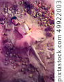 Young woman in pink ballet tutu surrounded by flowers 49922003