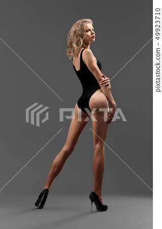Sexy blonde sportive body on grey background. 49923710