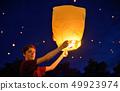 Teen boy in night with paper lantern 49923974