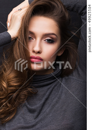 Portrait of a beautiful girl in a gray sweater on a black background 49925584