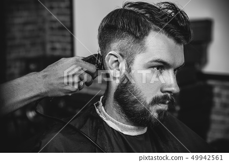 Young handsome barber making haircut for attractive man in barbershop 49942561