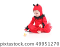 Baby with a red demon disguise watching a pacifier 49951270