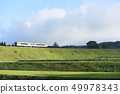 The first train and rice planting to finish going through the Koumi Line embankment where the Hokuto City Ogasazawa-cho, the morning sun hits 49978343